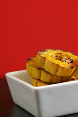 Yellow oven roasted squash with a red background