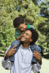 Father carrying son on shoulders in park.