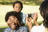 Woman photographing husband and son in park with camera. poster