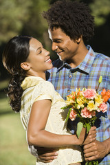 Man and woman holding flower bouquet and embracing each other.