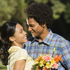Woman holding flower bouquet and embracing man smiling.
