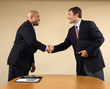 Fototapety Two businessmen in suits shaking hands and smiling.