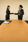Two businesswomen in suits shaking hands and smiling. poster