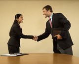 Two businesspeople in suits shaking hands and smiling. poster