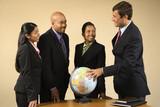 Corporate businesspeople standing around world globe. poster