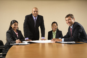 Businesspeople having a meeting at conference table smiling.