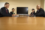 Businesspeople sitting at table with screen in background. poster