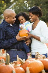 Parents and daughter picking out pumpkin at outdoor market.