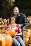 Portrait of happy smiling couple sitting in pumpkin patch. poster