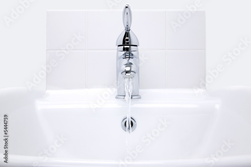 White modern ceramic handbasin and chrome tap, water running.