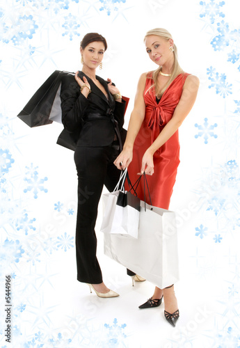 two happy girls with shopping bags and snowflakes