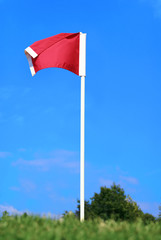 Red soccer corner flag against blue sky on green field