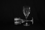 thin wine glasses againt a black background poster