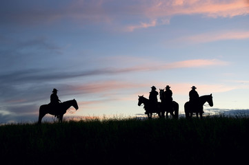 Cowboys silhouetted against a dawn sky. Montana horse ranch