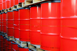 Assembly of red oil drums on palettes poster
