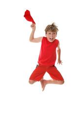 Zestful energetic boy jumps high off the floor hat in hand