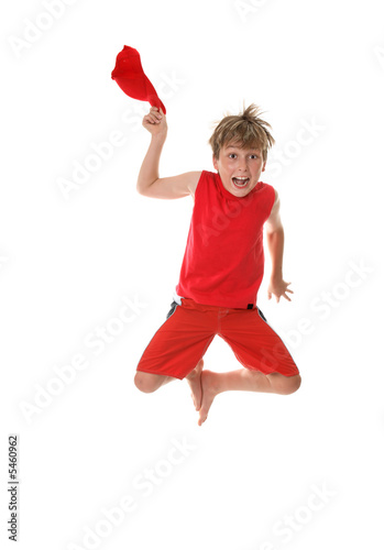 Zestful energetic boy jumps high off the floor hat in hand