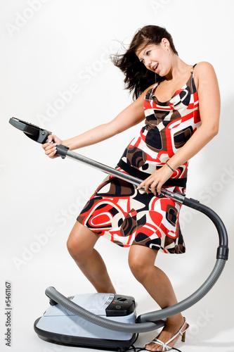 Frau spielt mit Staubsauger als Gitarre