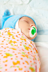 newborn infant in diaper with pacifier