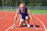 Senior runner in starting position on track poster