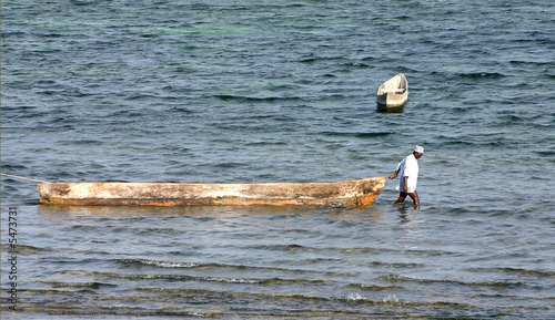 African man standing in water und pulling a boat