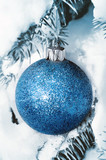 Christmas decoration hanging on snow covered spruce tree outside poster