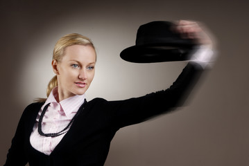 Dynamic studio photo of the woman moving her hat