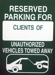 Image of a green reserved parking for clients only sign