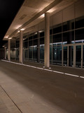 Modern arcade and glass walls by night poster