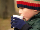 young boy with hat and gloves drinking hot chocolate outdoors