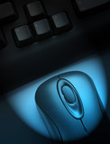Wireless keyboard and mouse with blue spotlight effect poster
