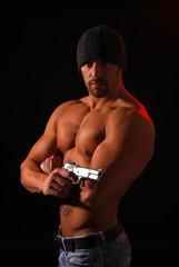 A muscular man at night with a gun
