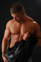 A handsome bodybuilder removing his shirt