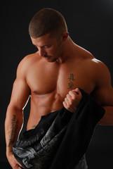 A handsome bodybuilder removing his shirt