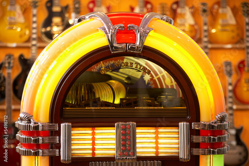 front view of a very colorful jukebox with guitars in the back - 5498712