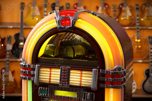 Leinwanddruck Bild jukebox in front of guitars - selective focus on jukebox