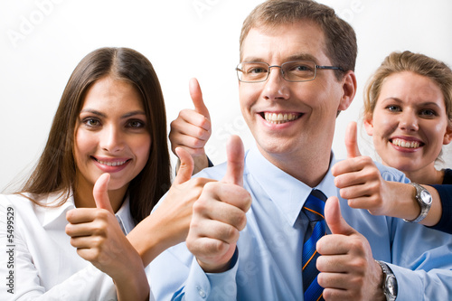 Team of three office worker's give the thumb's up sign