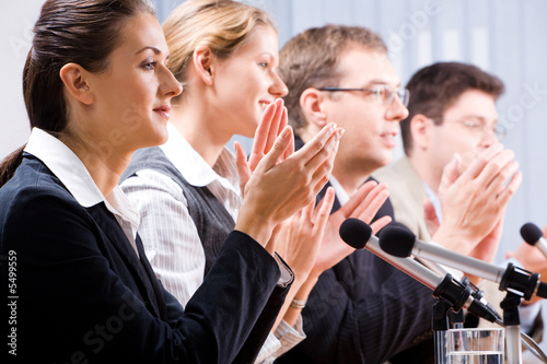 Portrait of several confident people clapping their hands