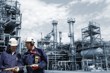 engineers and large oil refinery in blue