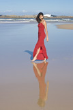 Lady in red dress walking at the beach