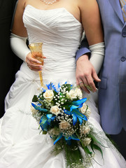 Hands of a bride holding bouquet and a glass of champagne