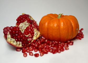 an autumnal pairing of a pomegranate and a pumpkin.