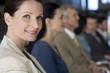 Confident businesswoman with team behind