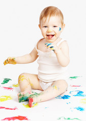 The smiling child sits among traces from water paints