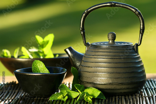 In de dag Thee Black iron asian teapot with sprigs of mint for tea