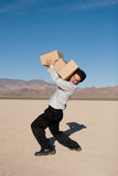 Businessman carrying heavy boxes poster