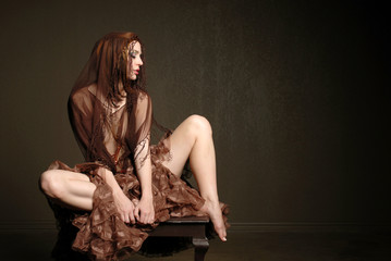 Beautiful woman wearing scarf sitting