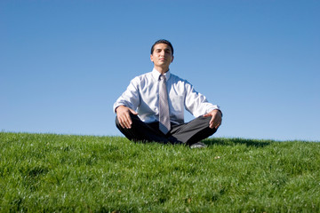 Businessman meditating on green grass