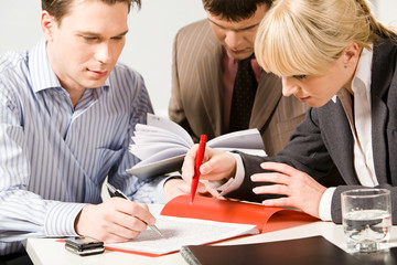 Business people pointing at a text of working document