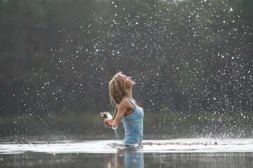 Girl plays with water and splashing small drops